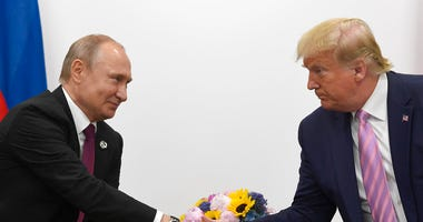 FILE - In this June 28, 2019, file photo President Donald Trump, right, shakes hands with Russian President Vladimir Putin, left, during a bilateral meeting on the sidelines of the G-20 summit in Osaka, Japan.