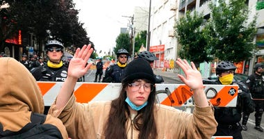 A protester stands with her hand up in front of a road blocked by Seattle police in the Capitol Hill Organized Protest zone early Wednesday, July 1, 2020. (AP Photo/Aron Ranen)