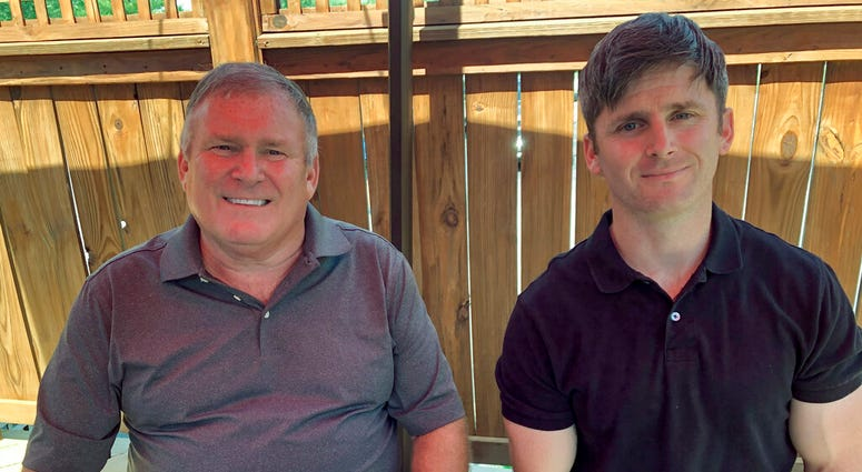 This photo from June 26, 2020 shows Buck Newsome, left, a Baby Boomer, and his son, Chris Newsome, of the Millennial generation, as they pose for a photo while having lunch together in Newtown, Ohio.  (AP Photo/Dan Sewell)
