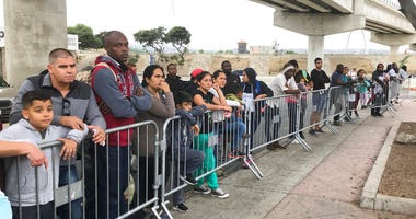 FILE - In this Thursday, Sept. 26, 2019 file photo asylum seekers in Tijuana, Mexico, listen to names being called from a waiting list to claim asylum at a border crossing in San Diego.