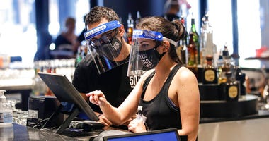 Bartenders were masks and face shields as they work at Slater's 50|50 in Wednesday, July 1, 2020, in Santa Clarita, Calif.