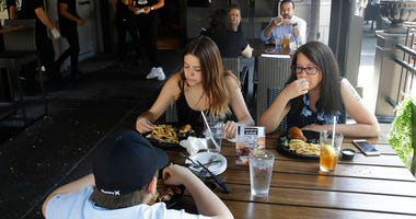 Patrons eat lunch at Slater's 50/50 Wednesday, July 1, 2020, in Santa Clarita, Calif.