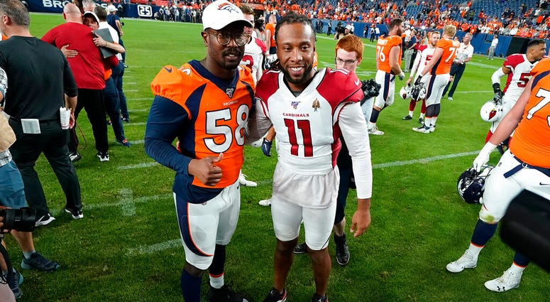 LE - In this Aug. 29, 2019, file photo, Denver Broncos outside linebacker Von Miller (58) greets Arizona Cardinals wide receiver Larry Fitzgerald (11) after an NFL preseason football game in Denver.