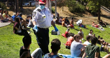 FILE - San Francisco Police Auxiliary Law Enforcement Response Team (ALERT) volunteer David Flynn offers face masks to help prevent the spread of the coronavirus at Dolores Park in San Francisco, Sunday, May 24, 2020.