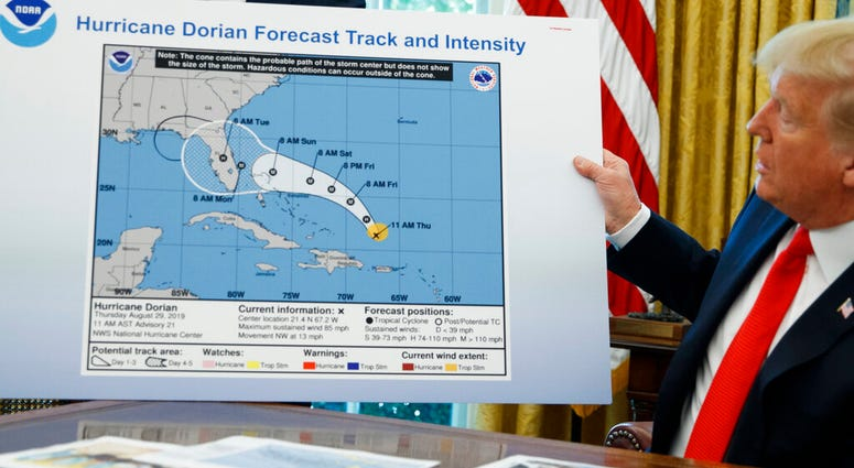 FILE - In this Sept. 4, 2019, file photo, President Donald Trump holds a chart as he talks with reporters after receiving a briefing on Hurricane Dorian in the Oval Office of the White House in Washington.