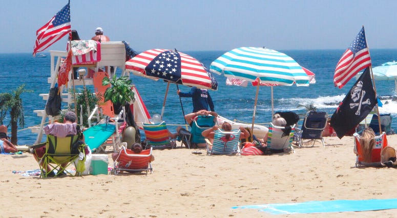 Flags line the beach in Belmar, N.J., on June 28, 2020. With large crowds expected at the Jersey Shore for the July Fourth weekend, some are worried that a failure to heed mask-wearing and social distancing protocols could accelerate the spread of the cor