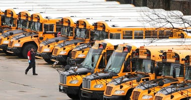 FILE - In this April 27, 2020, file photo, a worker passes public school buses parked at a depot in Manchester, N.H.