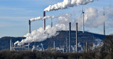 FILE-In this Jan. 16, 2020 file photo an uniper coal-fired power plant and BP refinery steam beside a wind generator in Gelsenkirchen, Germany.