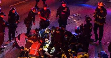 Emergency workers tend to an injured person on the ground after a driver sped through a protest-related closure on the Interstate 5 freeway in Seattle, authorities said early Saturday, July 4, 2020.