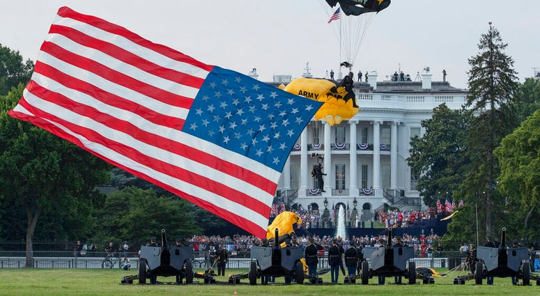 "President Donald Trump and first lady Melania Trump watch as the U.S. Army Golden Knights Parachute Team descend during a ""Salute to America"" event on the South Lawn of the White House, Saturday, July 4, 2020, in Washington."
