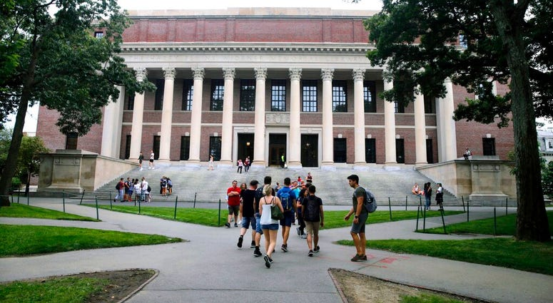 FILE - In this Aug. 13, 2019 file photo, students walk near the Widener Library in Harvard Yard at Harvard University in Cambridge, Mass.