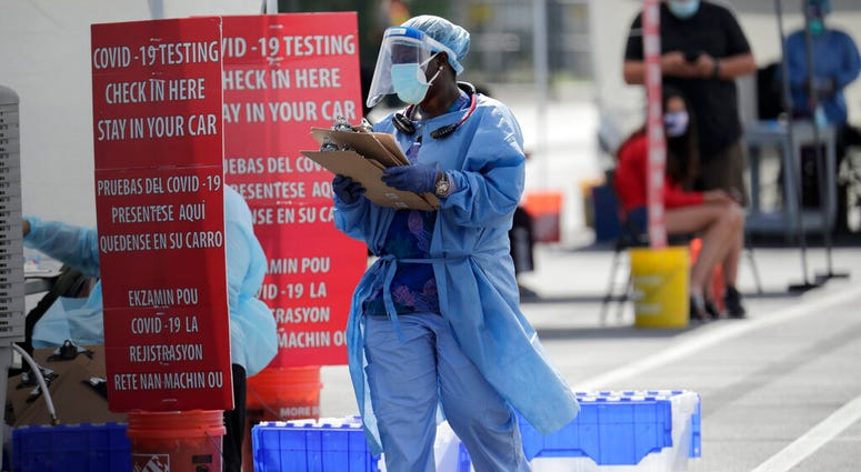 A health care worker works at a COVID-19 testing site sponsored by Community Heath of South Florida at the Martin Luther King, Jr. Clinica Campesina Health Center, during the coronavirus pandemic, Monday, July 6, 2020, in Homestead, Fla.
