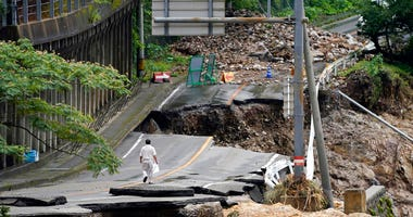 A man walks on heavily damaged road following a heavy rain in Kumamura, Kumamoto prefecture, southern Japan Monday, July 6, 2020. Rescue operations continued and rain threatened wider areas of the main island of Kyushu.