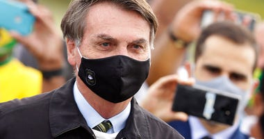 FILE - In this May 25, 2020, file photo, Brazil's President Jair Bolsonaro, wearing a face mask amid the coronavirus pandemic, stands among supporters as he leaves his official residence of Alvorada palace in Brasilia, Brazil.