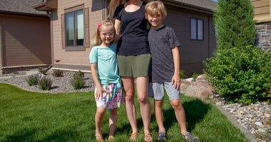 Tara Carlson poses for a photo with her children Kyler, 9, and Alayna, 6, outside their home in Omaha, Neb., Tuesday, July 7, 2020. Carlson pulled her kids out of summer camp at the last minute, losing $300 in deposits.