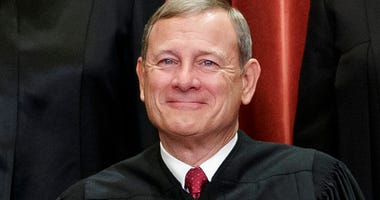 FILE - This Nov. 30, 2018, file photo shows Chief Justice of the United States, John Roberts, as he sits with fellow Supreme Court justices for a group portrait at the Supreme Court Building in Washington.