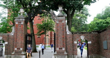 FILE - In this Aug. 13, 2019, file photo, pedestrians walk through the gates of Harvard Yard at Harvard University in Cambridge, Mass. (AP Photo/Charles Krupa, File)