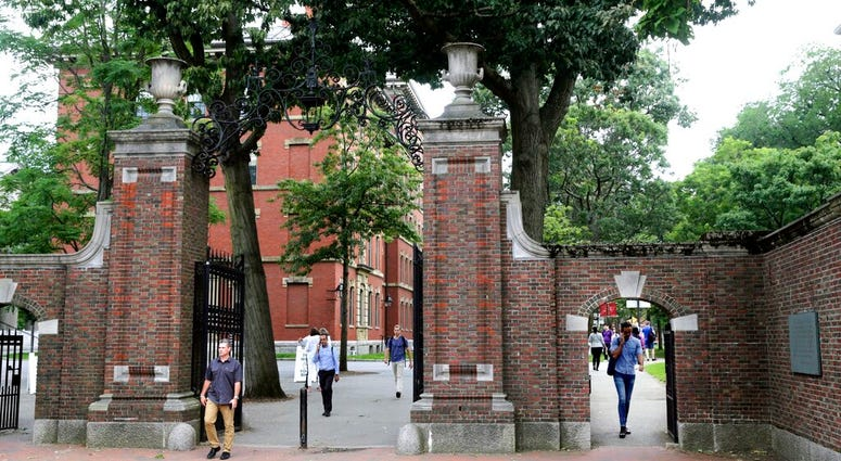 FILE - In this Aug. 13, 2019, file photo, pedestrians walk through the gates of Harvard Yard at Harvard University in Cambridge, Mass. (AP Photo/Charles Krupa, File)