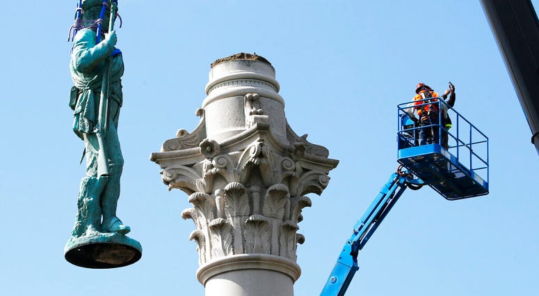 Crews remove the Confederate Soldiers & Sailors Monument in Libby Hill Park, Wednesday, July 8, 2020, in Richmond, Va.