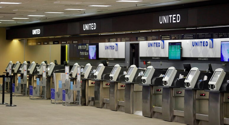 FILE - In this April 24, 2020 file photo, empty United Airlines ticket machines are shown at the Tampa International Airport in Tampa, Fla.