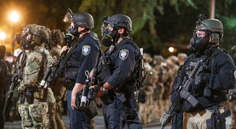 In this photo provided by Doug Brown, agents from different components of the Department of Homeland Security are deployed to protect a federal courthouse in Portland, Ore., on Sunday, July 5, 2020.