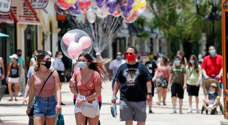 FILE - In this June 16, 2020, file photo, guests required to wear masks because of the coronavirus stroll through the Disney Springs shopping, dining and entertainment complex in Lake Buena Vista, Fla.