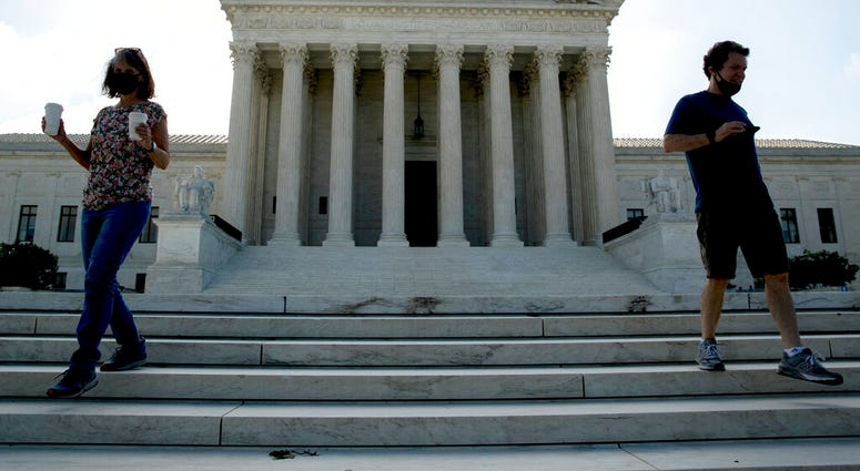 Two people walk down the steps outside the Supreme Court, Thursday, July 9, 2020, in Washington.