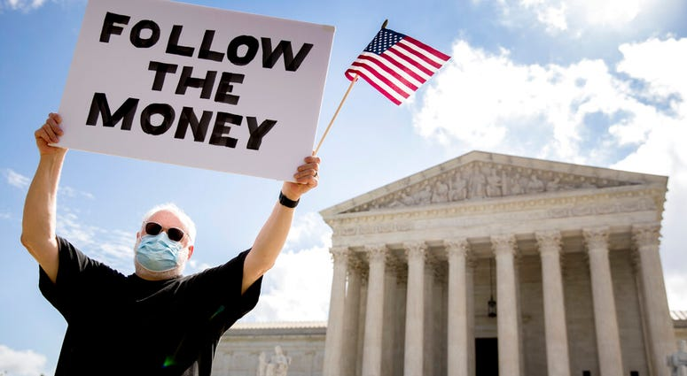 "Bill Christeson holds up a sign that reads ""Follow the Money"" outside the Supreme Court, Thursday, July 9, 2020, in Washington."