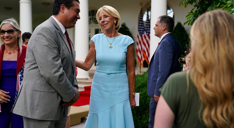 """Education Secretary Betsy DeVos speaks with Jesus Marquez, President of Marquez Group Strategies, after President Donald Trump signed an executive order on the """"White House Hispanic Prosperity Initiative,"""" in the Rose Garden of the White House, Thursday,"""