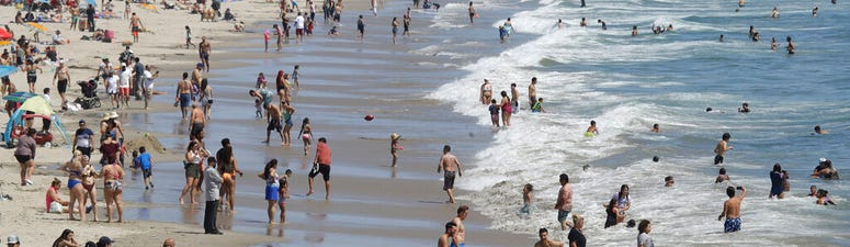 Visitors crowd the beach Sunday, July 12, 2020, in Santa Monica, Calif., amid the coronavirus pandemic.