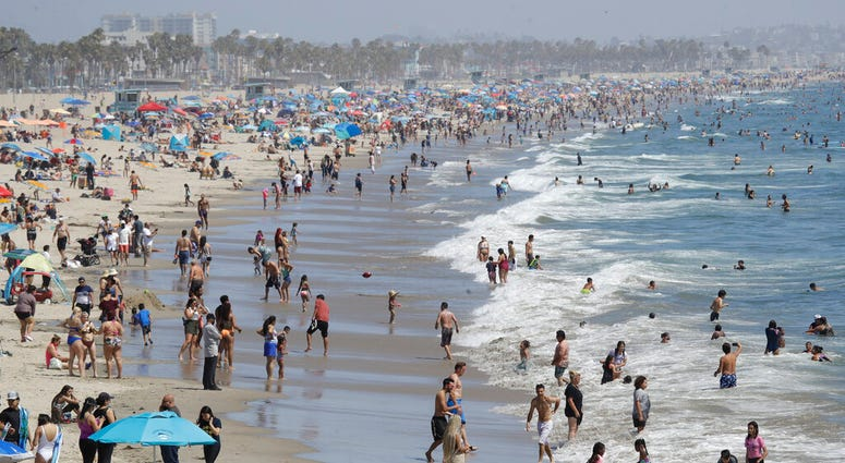 Visitors crowd the beach Sunday, July 12, 2020, in Santa Monica, Calif., amid the coronavirus pandemic.