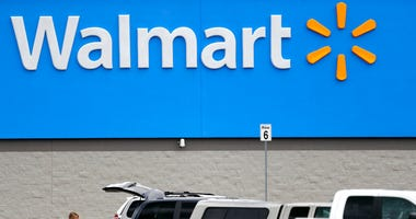FILE - In this March 31, 2020 file photo, a woman pulls groceries from a cart to her vehicle outside of a Walmart store in Pearl, Miss.
