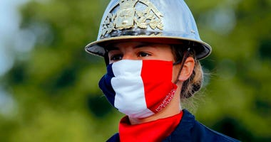 FILE - In this July 14, 2020, file photo, a firefighter wears a face mask with the colors of the French flag, prior to the Bastille Day parade on the Champs-Élysées avenue in Paris.