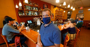 Nick Gavrilides, the owner of the Soup Spoon, poses at one of his two restaurants in Lansing, Mich., Thursday, July 16, 2020.  (AP Photo/Paul Sancya)