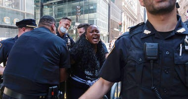 NYPD officers detain a protester who poured black paint on the Black Lives Matter mural outside of Trump Tower on Fifth Avenue in the Manhattan borough of New York on Saturday, July 18, 2020.
