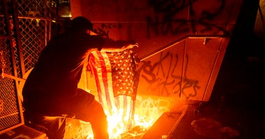 A Black Lives Matter protester burns an American flag outside the Mark O. Hatfield United States Courthouse on Monday, July 20, 2020, in Portland, Ore. (AP Photo/Noah Berger)