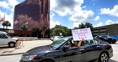 FILE - In this Tuesday, July 7, 2020 file photo, a teacher holds up a sign while driving by the Orange County Public Schools headquarters as educators protest in a car parade around the administration center in downtown Orlando, Fla. (Joe Burbank/Orlando