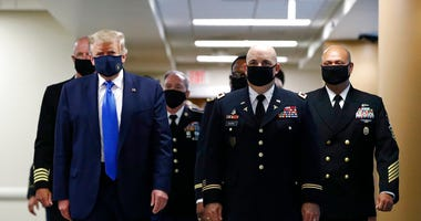 FILE - In this July 11, 2020, file photo President Donald Trump, foreground left, wears a face mask as he walks with others down a hallway during a visit to Walter Reed National Military Medical Center in Bethesda, Md. (AP Photo/Patrick Semansky, File)