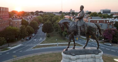 FILE - In this July 31, 2017 file photo, the sun sets behind the statue of confederate General Robert E. Lee on Monument Avenue in Richmond, Va. (AP Photo/Steve Helber)
