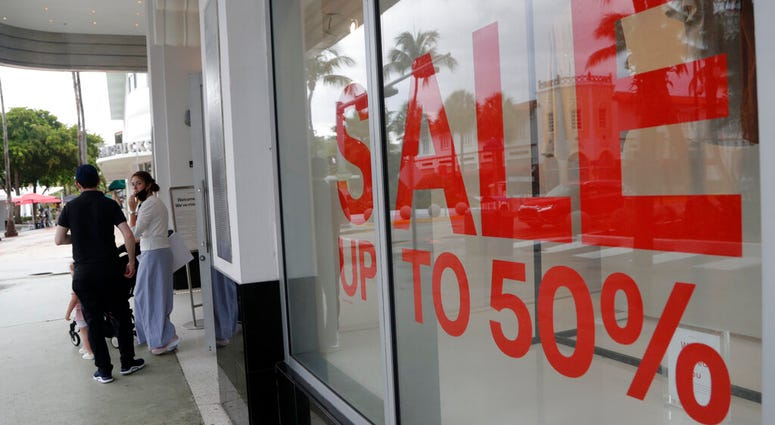 FILE - In this June 17, 2020 file photo, a sign advertises a sale at an H&M store along Lincoln Road Mall in Miami Beach, Fla.
