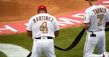 Washington Nationals manager Dave Martinez (4) and shortstop Trea Turner (7) kneel and hold a piece of black fabric before an opening day baseball game against the New York Yankees at Nationals Park, Thursday, July 23, 2020, in Washington.