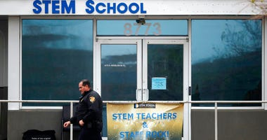 FILE - In this May 8, 2019, file photo, a Douglas County, Colo., Sheriff's deputy walks past the doors of the STEM Highlands Ranch school in Highlands Ranch, Colo.