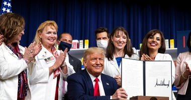President Donald Trump holds up a signed executive order on lowering drug prices, in the South Court Auditorium in the White House complex, Friday, July 24, 2020, in Washington.