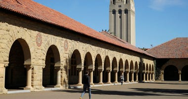 FILE- In this March 14, 2019, file photo, people walk on the Stanford University campus beneath Hoover Tower in Stanford, Calif.