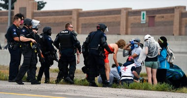 CORRECTS TO POLICE BELIEVE WAS SHOT BY A FELLOW PROTESTER-Aurora Police officers and protest medics attend to an injured demonstrator who police believe was shot by a fellow protester while on Interstate 225, Saturday, July 25, 2020. (Andy Cross/The Denve