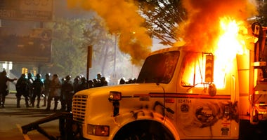 Police stand in front of a utility vehicle that was set on fire by protesters during a demonstration outside the Richmond Police Department headquarters on Grace Street in Richmond, Va., Saturday, July 25, 2020.