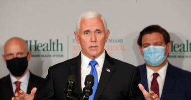 Vice President Mike Pence, center, gestures as he speaks during a news conference with Food and Drug Administration Commissioner Dr. Stephen Hahn. (AP Photo/Wilfredo Lee)