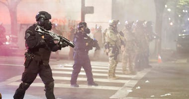 Federal officers deploy tear gas and crowd control munitions at demonstrators during a Black Lives Matter protest at the Mark O. Hatfield United States Courthouse Tuesday, July 28, 2020, in Portland, Ore. (AP Photo/Marcio Jose Sanchez)