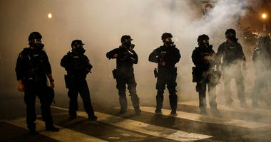 Federal officers are surrounded by smoke as they push back demonstrators during a Black Lives Matter protest at the Mark O. Hatfield United States Courthouse Wednesday, July 29, 2020, in Portland, Ore. (AP Photo/Marcio Jose Sanchez)