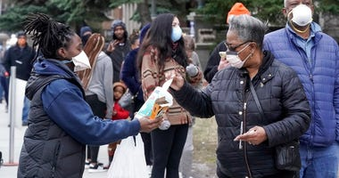 FILE - In this April 7, 2020, file photo, a worker hands out disinfectant wipes and pens as voters line up outside Riverside High School for Wisconsin's primary election in Milwaukee.